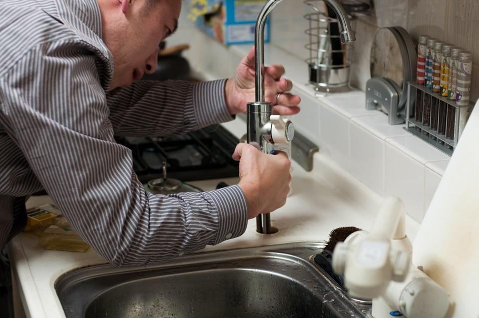 a plumber fixing a sink fixture