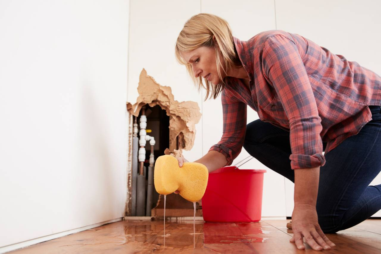 Woman wiping up water from floor